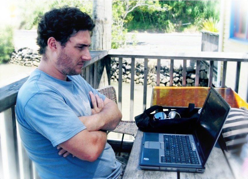 A man waits on a rural porch for a website to load on his Dell laptop.